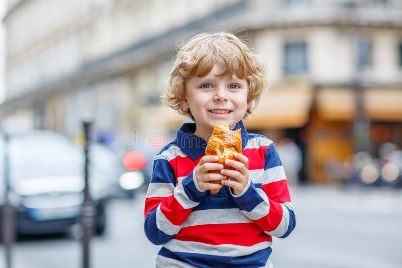 Little cute child on a street of city eating fresh croissant. Happy cute boy on a street of city eating fresh croissant, on warm day. Paris, France stock image