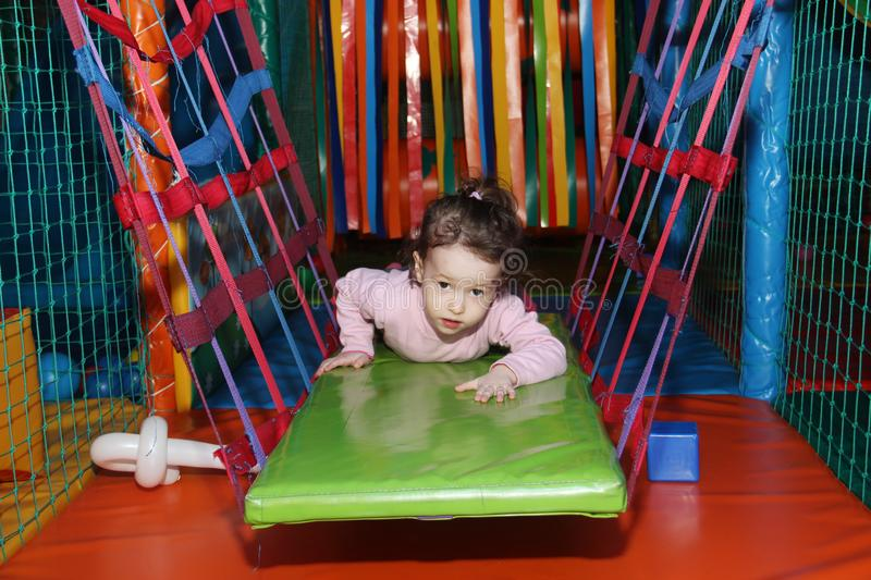 Little cute curly baby girl playing in a children`s entertainment center in the game maze. The child plays in the playground stock photos
