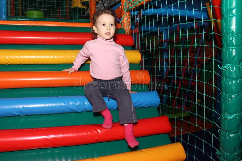 Little cute curly baby girl playing in a children`s entertainment center in the game maze. The child plays in the playground stock image