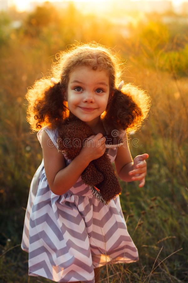 Little cute curly girl hugd a fluffy toy owl. Toddler girl play with sweet doll. A beautiful sunlight, warm colours. Autumn time stock photo
