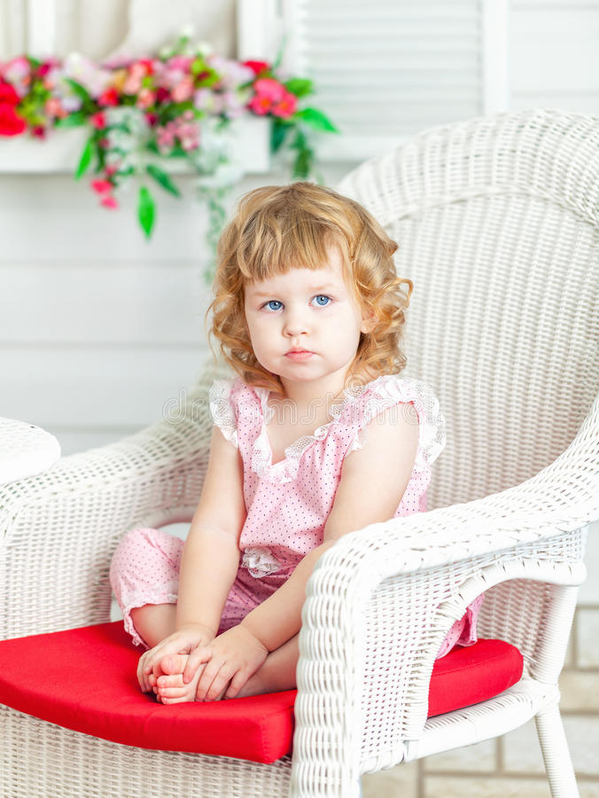 Little cute curly girl sitting on white wicker chair in the garden and looks into distance. royalty free stock photography