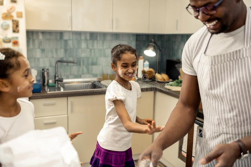Little cute daughter having fun while using flour when cooking. Having fun. Little cute dark-haired daughter having fun while using flour when cooking royalty free stock photography