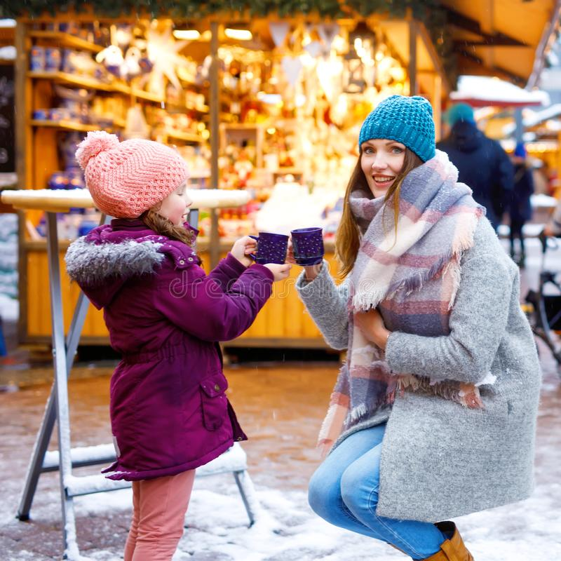 Little cute daughter and mother with cup of steaming hot chocolate or children punch. Happy child girl and beautiful royalty free stock photo