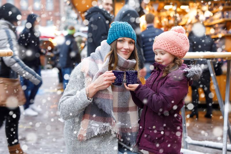 Little cute daughter and mother with cup of steaming hot chocolate or children punch. Happy child girl and beautiful women on Christmas market in Germany stock image