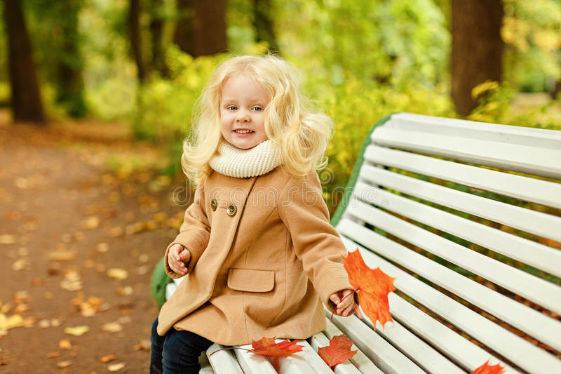 Little cute fluffy blonde girl in a coat sitting on a bench in t stock photos