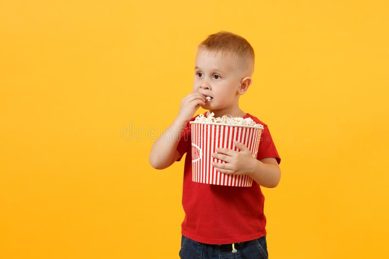 Little cute fun kid baby boy 3-4 years old in red t-shirt holding bucket for popcorn, eating fast food isolated on royalty free stock image