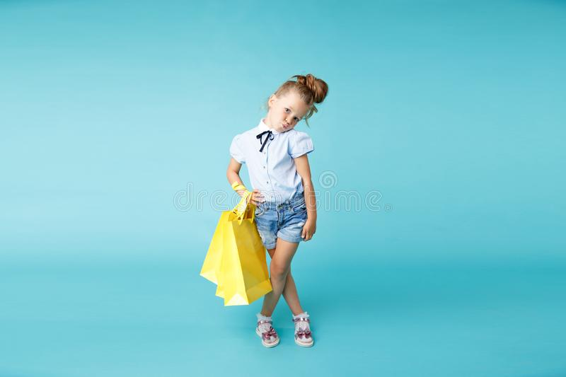 Little cute and funny girl holding big bright colored yellow paper bags in the blue studio. royalty free stock images