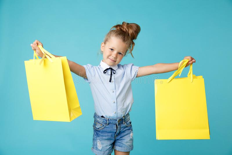 Little cute and funny girl holding big bright colored yellow paper bags in the blue studio. royalty free stock image