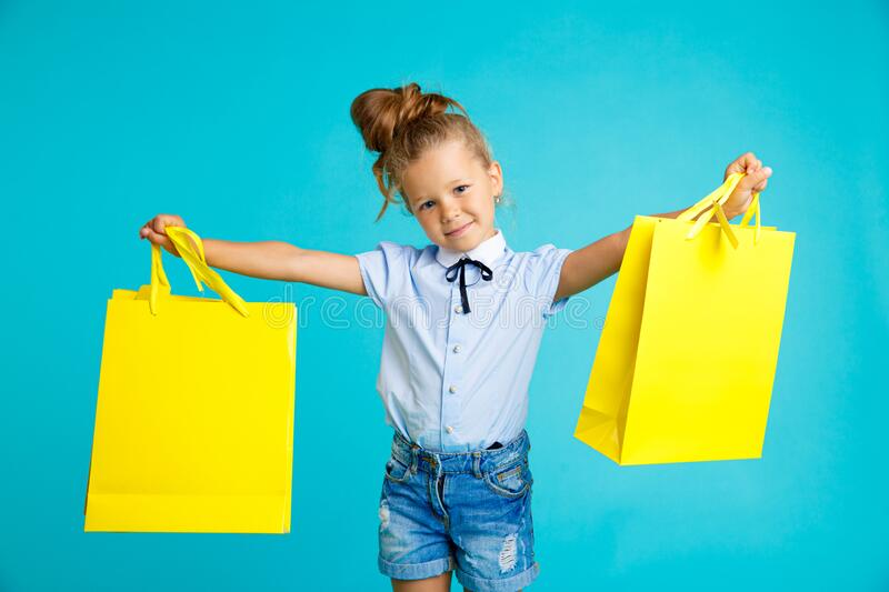 Little cute and funny girl holding big bright colored yellow paper bags in the blue studio. stock image