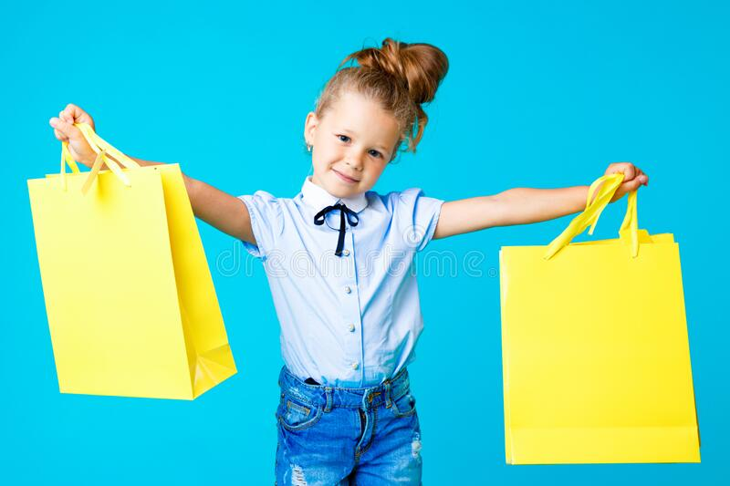 Little cute and funny girl holding big bright colored yellow paper bags in the blue studio. stock photo
