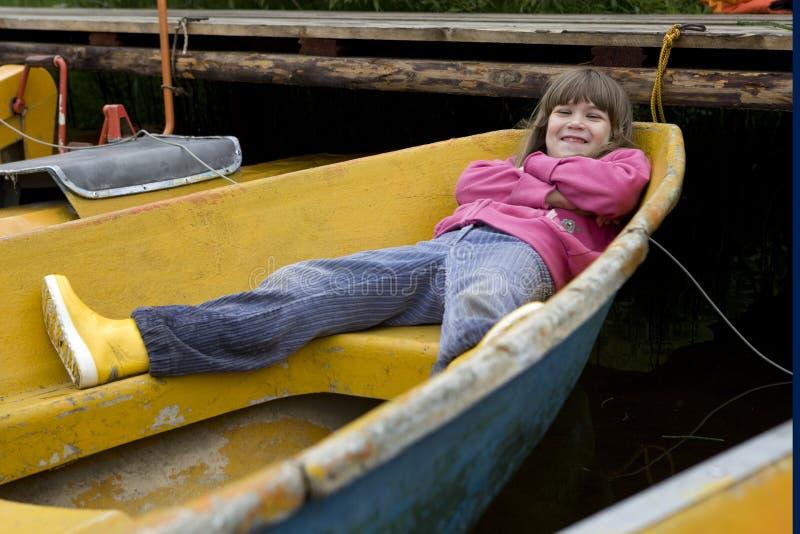 Little cute funny girl lying in boat stock photo