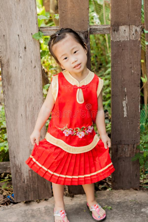Little Cute Girl act to innicent wearing chinese new year. Little of Cute Girl act to innicent wearing chinese new year royalty free stock image