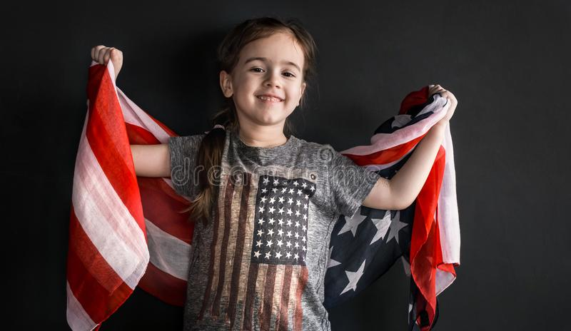 Little girl with the American flag. Little cute girl with the American flag on a dark background, the concept of America`s Day and patriotism royalty free stock photos