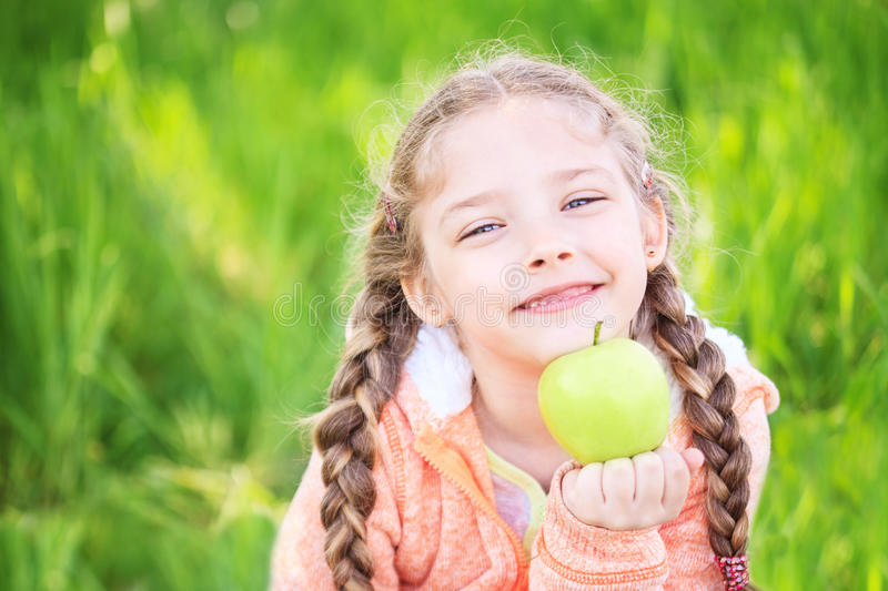 Little cute girl on a background of green grass with an apple royalty free stock image