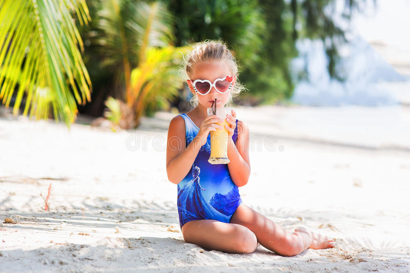 Little cute girl on the beach in a bathing suit, sunglasses, sitting under a palm tree, drinking exotic cocktail stock image