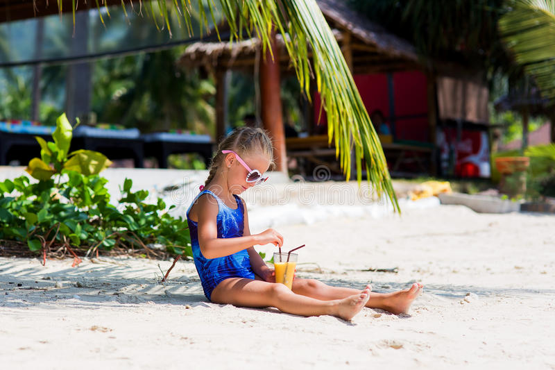 Little cute girl on the beach in a bathing suit, sunglasses, sitting under a palm tree, drinking exotic cocktail royalty free stock photo