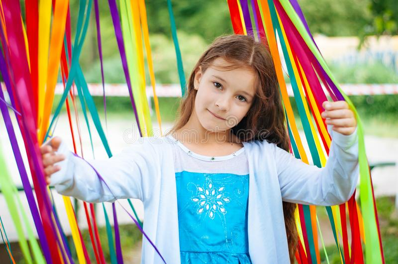 Little cute girl in a beautiful dress near the photo zone of festive ribbons royalty free stock photos