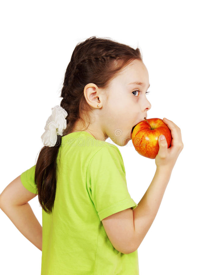 Little cute girl bites a big red apple royalty free stock photography
