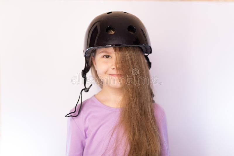 Little cute girl in the black helmet, with her hair covering one eye, on a light background stock photos