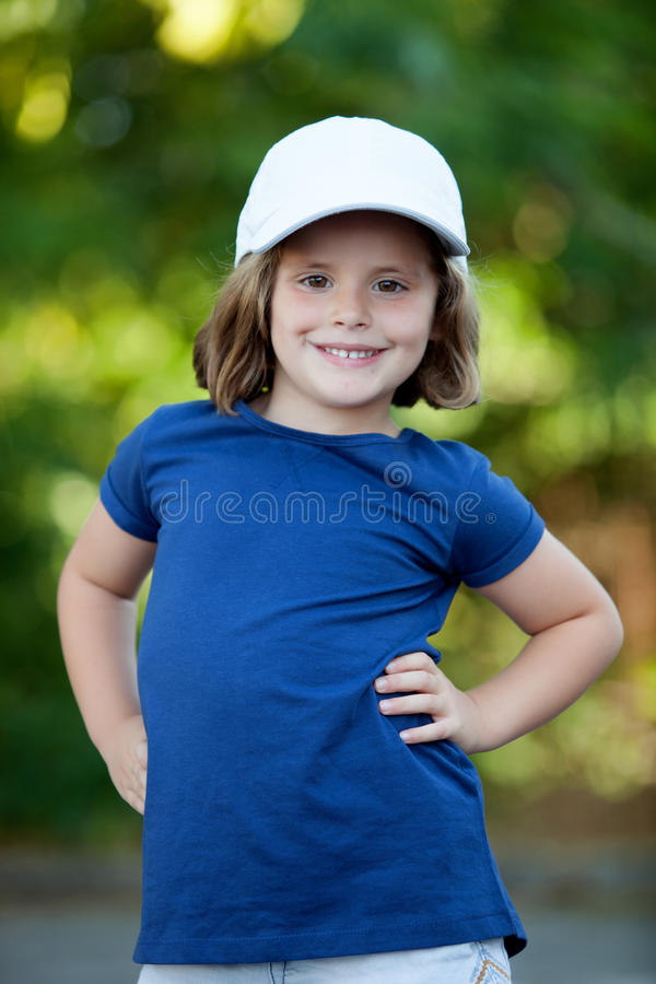 Little cute girl with a cap in the park stock images