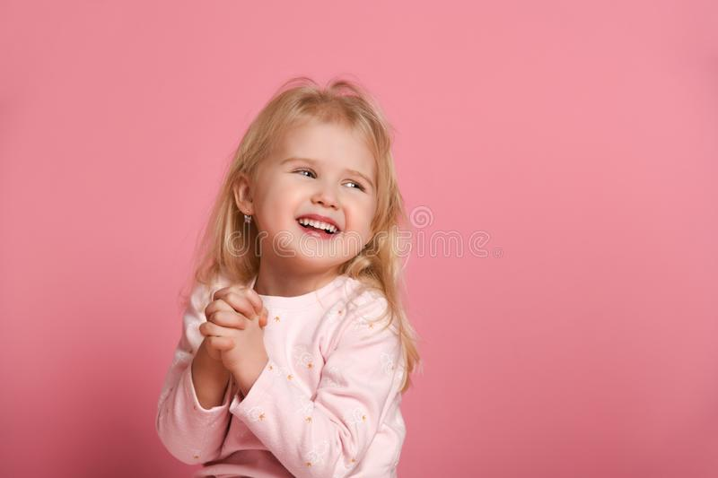 Little cute girl child blonde in a pink suit is shy on a pink background royalty free stock image