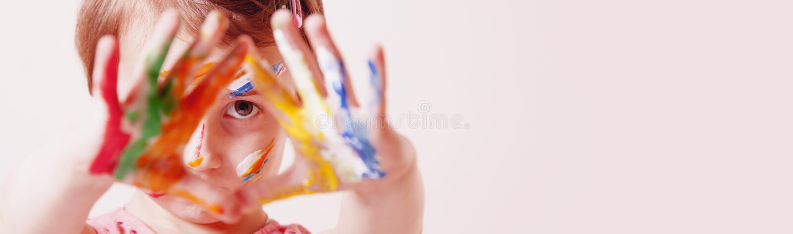 Close up little cute girl with children`s colorful makeup showing painted hands. Happy childhood and art concept. Selective focus stock image