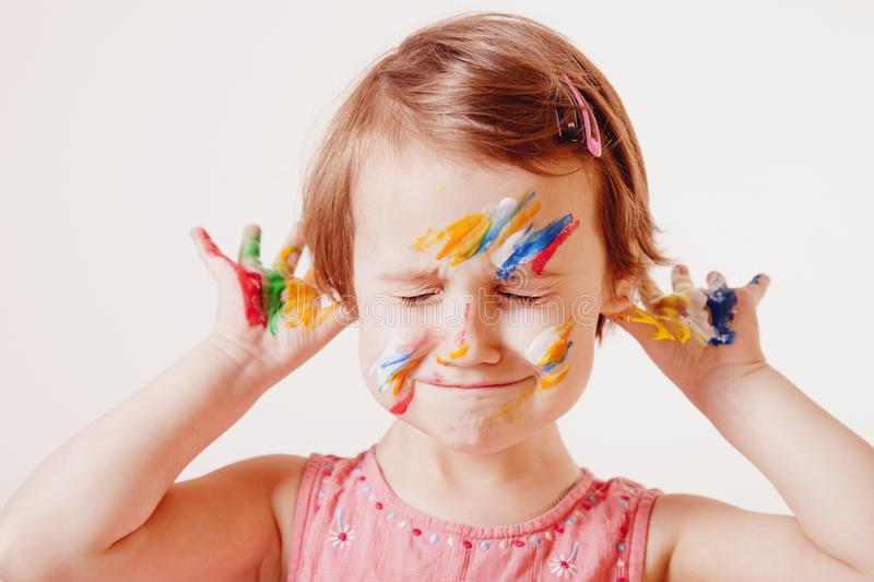 Funny portrait of cute cheerful child girl colourful painted hands and fac stock photography