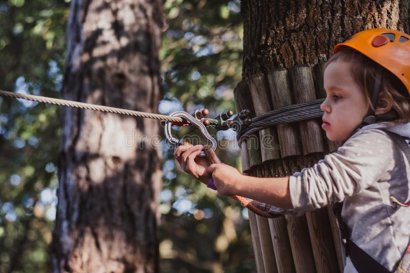 Little cute girl climbing in high rope course enjoying the adventure stock photography