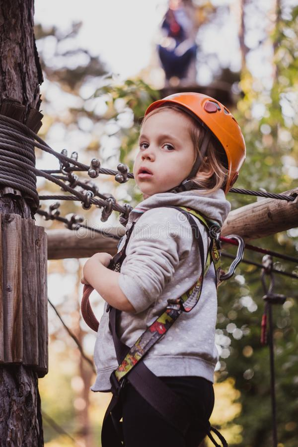 Little cute girl climbing in high rope course enjoying the adventure royalty free stock image