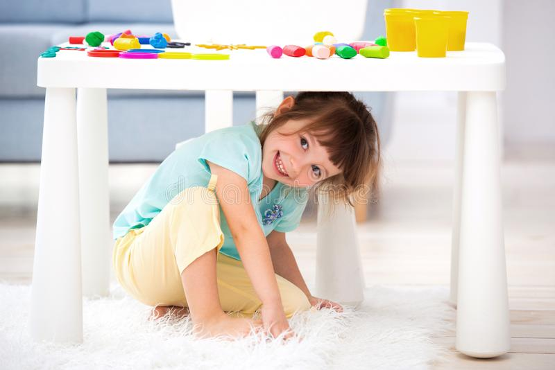 Little cute girl crawled under the table. The kid smiles, plays hide and seek stock image