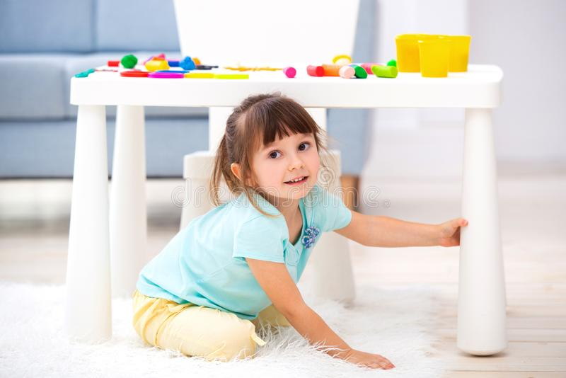 Little cute girl crawled under the table. The kid smiles, plays hide and seek royalty free stock photography