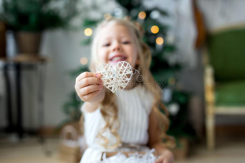 A little cute girl dreams of gifts. Girl making a wish. Merry Christmas and Happy Holidays royalty free stock photography