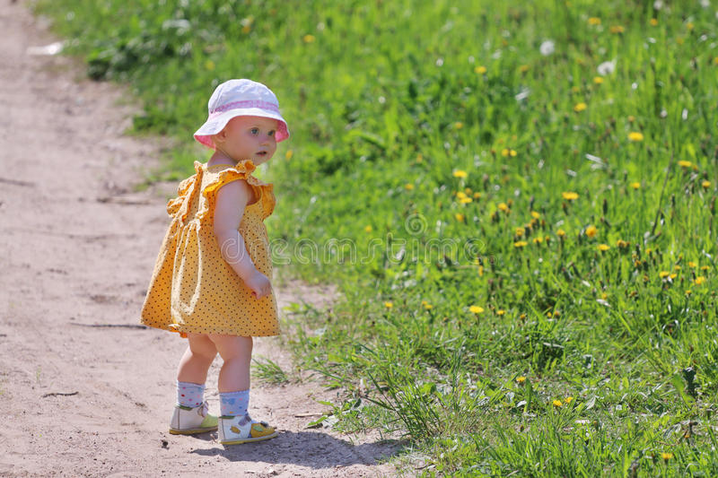 Little cute girl in dress goes on path near green grass. At summer day stock photography
