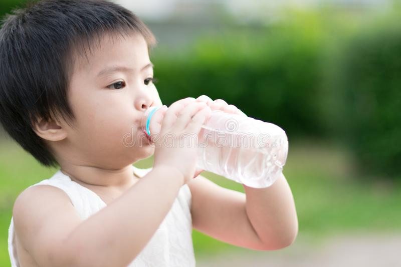 Little cute girl drinking clean water from plastic bottle stock images