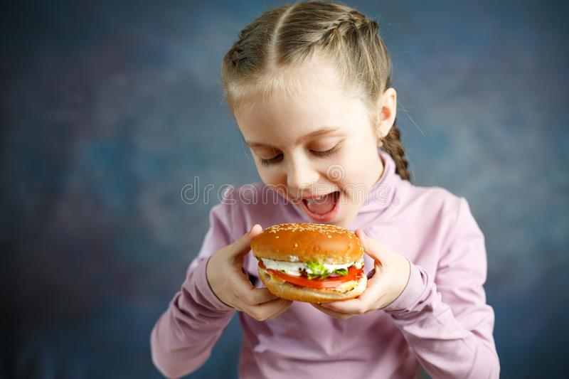 Little cute girl eating a Burger in a cafe, concept of a children`s fast food meal stock photos