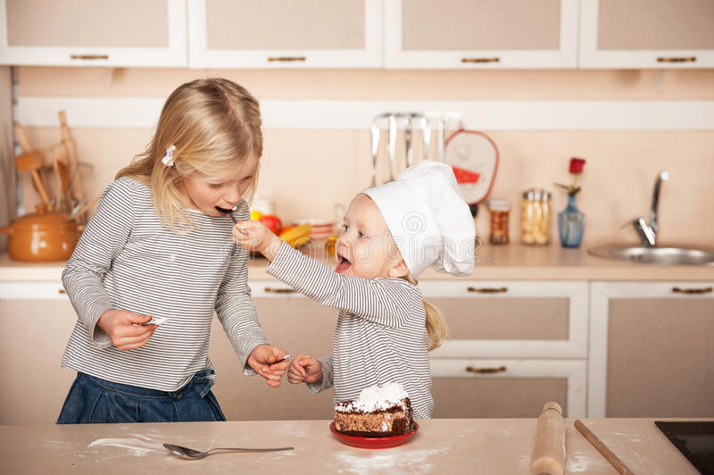 Little cute girl feeding her older sister cake royalty free stock images