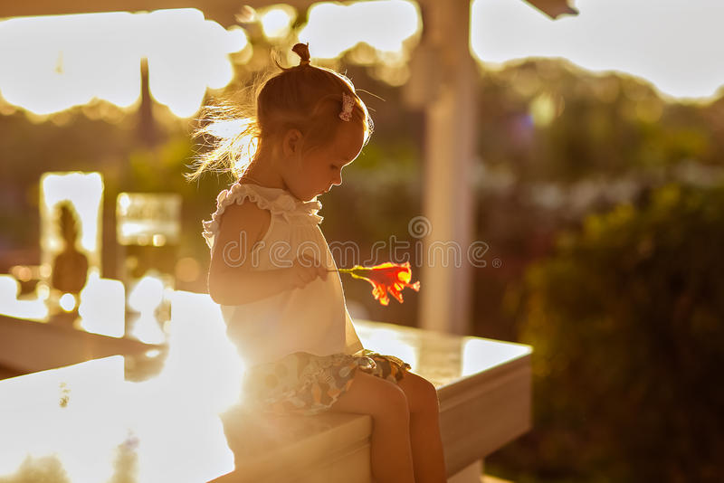 Little cute girl with flower in her hand sitting on the table royalty free stock photo