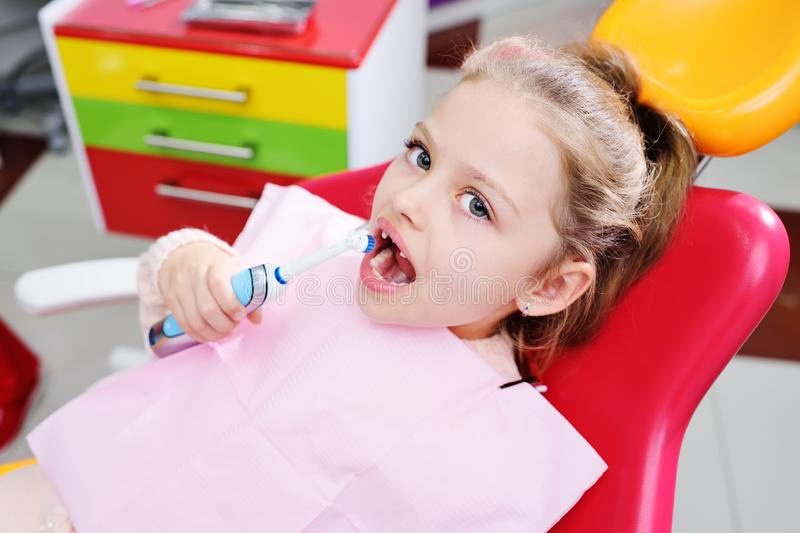 Little cute girl without front milk teeth in red dental chair with electric automatic toothbrush in hands. stock images