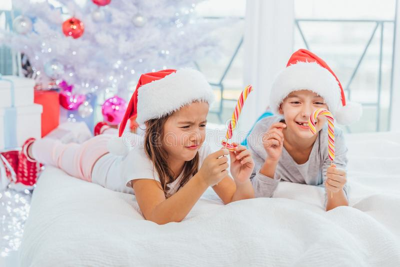 Little cute girl is frowning because she`ve broken her striped candycane. Her brother enjoys yummy lollipop. Small challenges of small kids concept royalty free stock photos