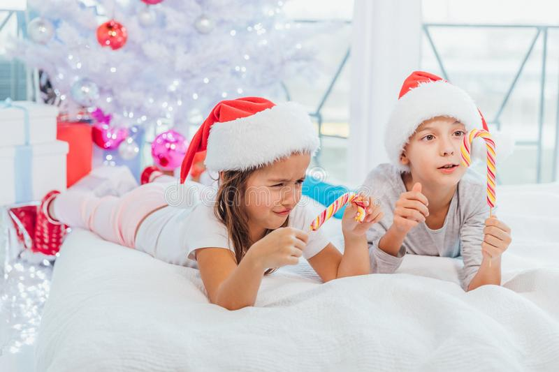 Little cute girl is frowning because she`ve broken her striped candycane. Her brother enjoys yummy lollipop. Small challenges of small kids concept stock image
