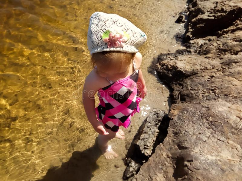 Little cute girl in full growth standing in shallow water in the river stock photos