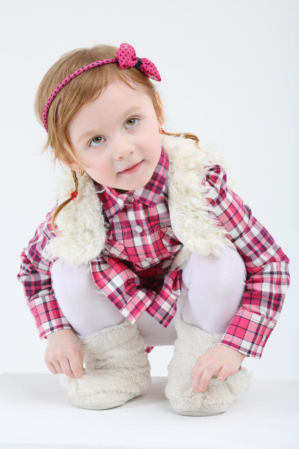 Download Little Cute Girl In Fur Vest And Boots Sits And Looks Up Stock Photo - Image: 34550292