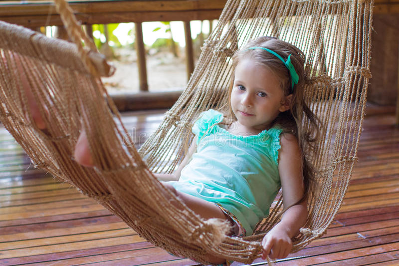 Little cute girl in a hammock on the terrace of royalty free stock images