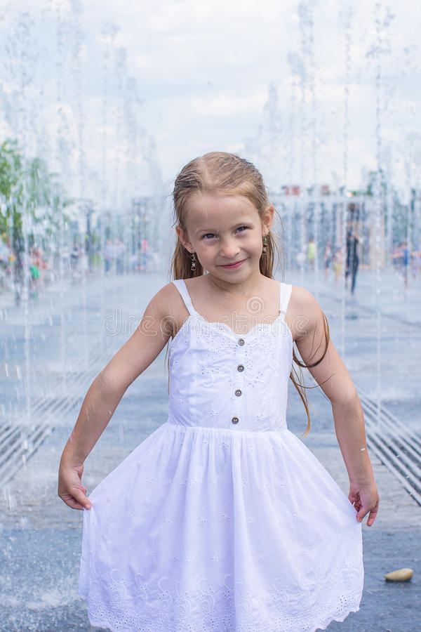 Little cute girl have fun in open street fountain royalty free stock images