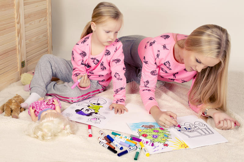 Little cute girl with her mom drawing royalty free stock image