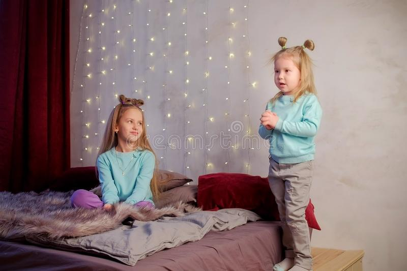 Little cute girl with her sister tells the poem in bedroom at home, children. royalty free stock photo