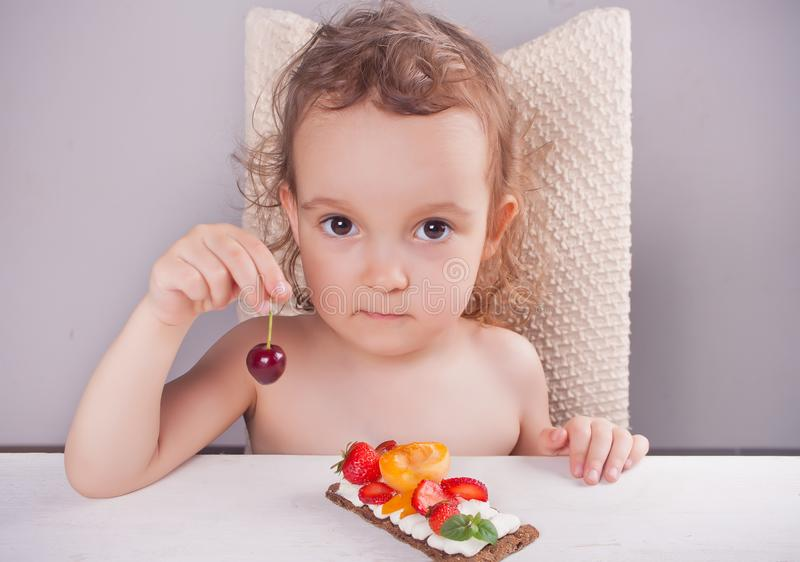 Little cute girl holding cherry in a hand and eating crisp bread with creme cheese, fruit and berries royalty free stock images