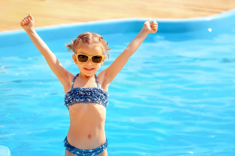 Little cute girl holding hands up near a swimming pool stock photos