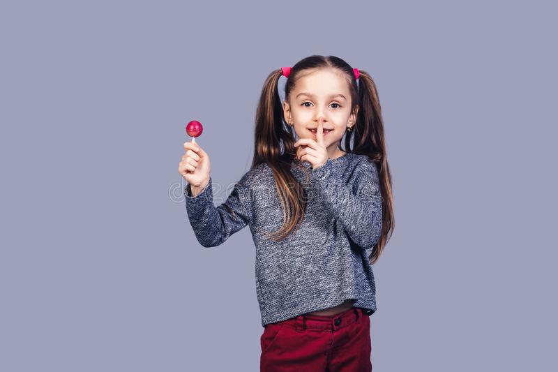 Little cute girl holds red lollipop in hand and shows shh. royalty free stock photography