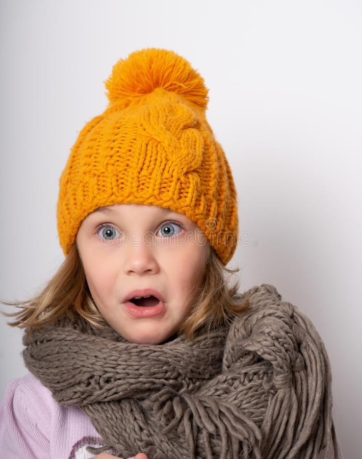 Little cute girl in a knitted hat and warm scarf looks surprised in shock stock image